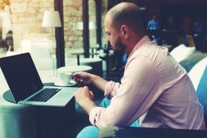 Modern business man connecting to wireless on his laptop computer during coffee break in modern interior, male freelancer working on notebook sitting in cafe, entrepreneur hold cup of tea or coffee